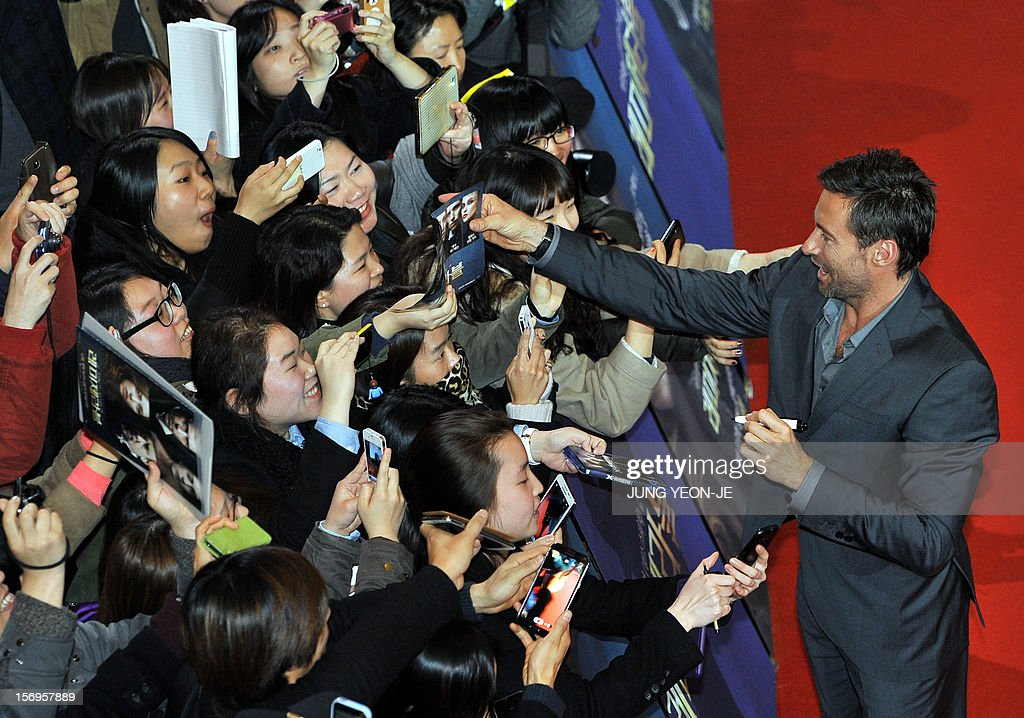 Sydney-born Hollywood star actor Hugh Jackman (R) signs autographs for South Korean fans after a press conference to promote his film 'Les Miserables' at a hotel in Seoul on November 26, 2012. The film will open in December in South Korea.