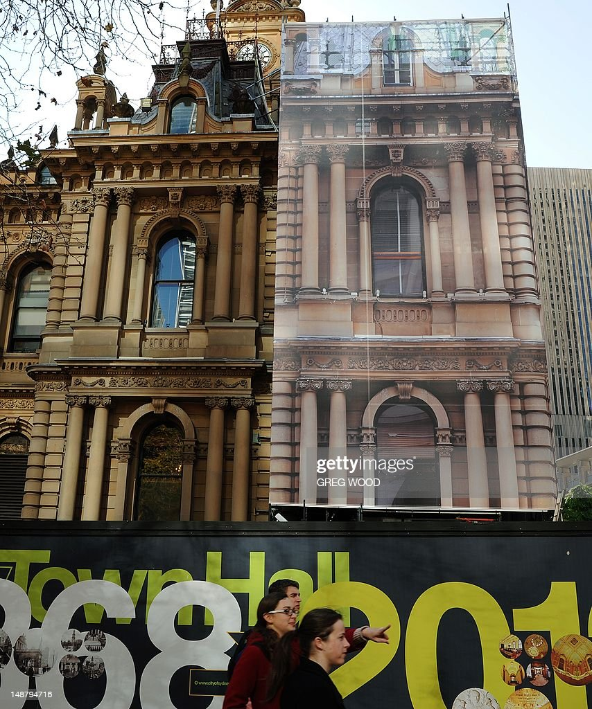 Sydney's iconic Town Hall building with its prominent sandstone facade is shown wrapped with a 20-metre-high mirror-image photograph, printed onto a custom-made mesh, on July 20, 2012. Behind the photograph the first stage of an extensive four-year conservation project has begun, with restoration work being carried out on the front facade of the building and the clocktower. Seismic bracing work has also begun and will include the installation of metal reinforcements behind the clocktower columns, made from a high-tech stainless steel that is normally used to make submarine propellers. AFP PHOTO / Greg WOOD
