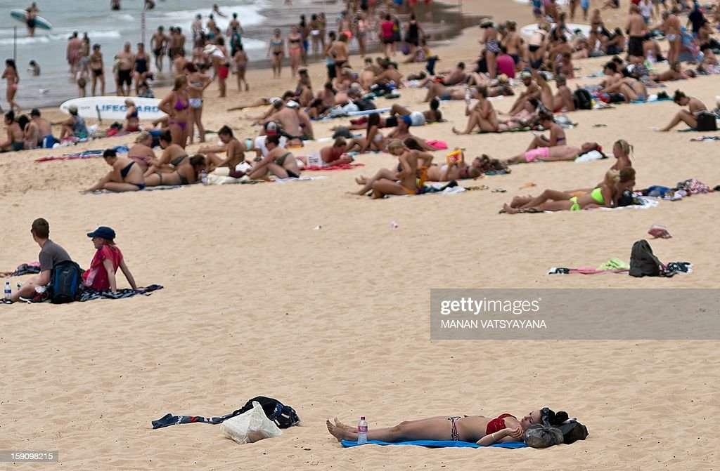 Sydneysiders and tourists gather on Manly beach in Sydney on January 8, 2013. Authorities warned New South Wales state faced one of the highest-risk fire days in its history, and temperatures rapidly climbed above 40 degrees Celsius (104 degrees Fahrenheit). AFP PHOTO/ MANAN VATSYAYANA