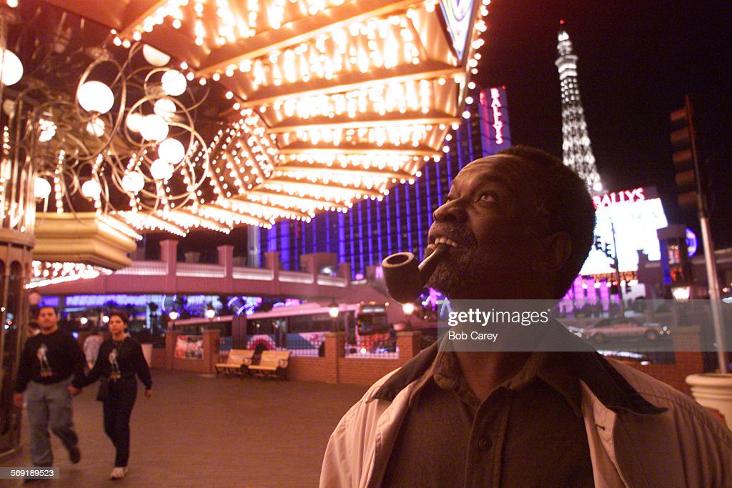 Syl Cheney–Colker smokes his pipe and observes the lights of a Las Vegas Strip casino where he is the first writer in exile Las Vegas has been...