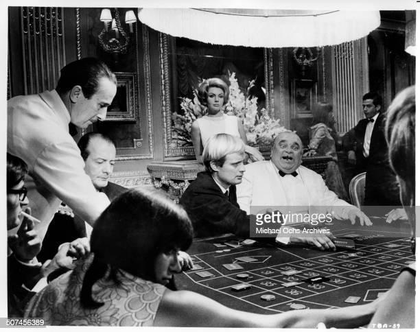 Sylva Koscina observes David McCallum winning streak at a casino in a scene from the MGM movie 'Three Bites of the Apple' circa 1967