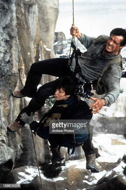 Sylvester Stallone and Janine Turner hanging by ropes off the side of a cliff in a scene from the film 'Cliffhanger' 1993