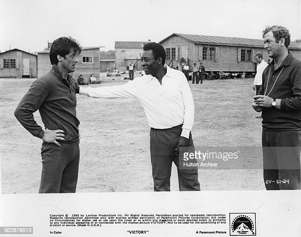 Sylvester Stallone is patted by Pele as Michael Caine looks on in a scene for the Paramount Pictures movie 'Victory' circa 1980