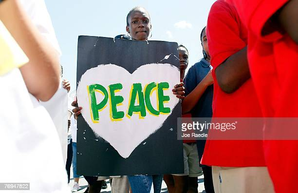 Sylvier JeanCharles holds a peace sign as she participates in The International Day of Peace September 21 2007 in Miami Florida The peace gathering...