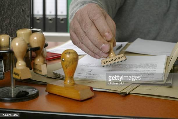 Symbol Buerokratie Behoerde Amt Beamter am Arbeitsplatz stempelt eine Akte mit dem Stempel 'erledigt'
