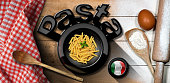 Black symbol with the Italian Pasta called Penne and flag in a wooden bowl, on a table with kitchen utensils, flour, egg and a checkered tablecloth