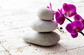 symbol of mindfulness, meditation and elegance with stack of balancing stones or pebbles over beautiful flowers and limestone background, copy space