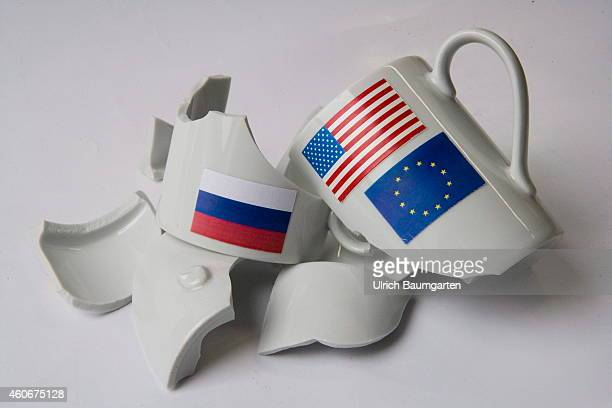 Symbol photo about sanctions of the EU and the USA against Russia Our picture shows a broken cup with the flags of the EU the USA and Russia on...