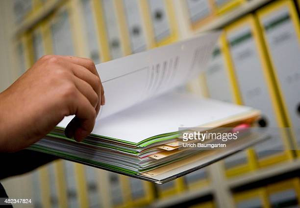 Symbol photo bureaucracy hands holding a file folder in front of a file shelving