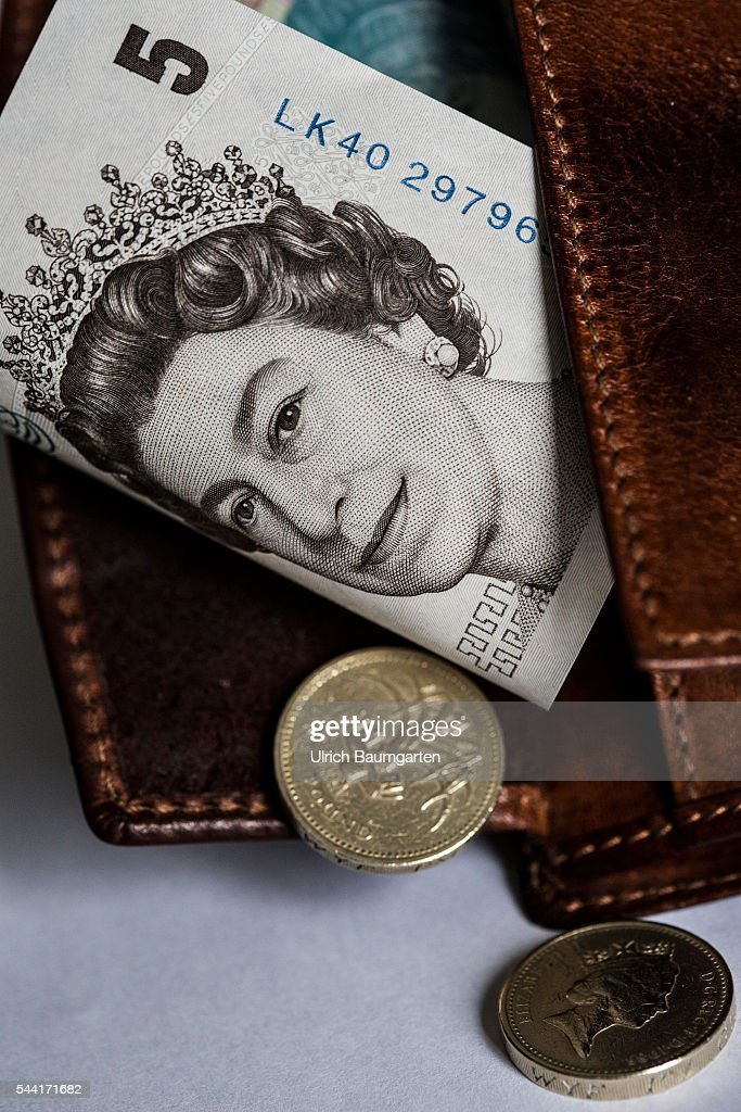 Symbol photo on the subjects Brexit, British Pounds Sterling, financel market, stock exchange, etc. The photo shows a wallet with a British 5 Pounds banknote and a 1 Pounds coin (front and back side).