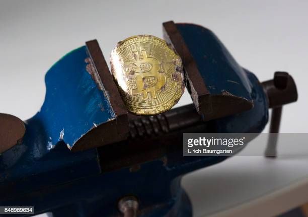 Symbol photo on the topics of Bitcoin Crypto currency financial speculation digital currency China etc Bitcoin in a vise