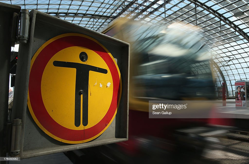 A symbol with a human figure on it marks the end of a train platform at Hauptbahnhof main railway station on August 13, 2013 in Berlin, Germany. A lack of personel due to sick leave and vacations has forced German state rail carrier Deutsche Bahn to severely restrict rail service at the main station in the city of Mainz, and the issue has snowballed into a political bonfire. Critics charge cuts in pursuit of privatizing Deutsche Bahn have led to a lack of investment in new trainees and that service will likely be threatened at other stations across Germany as well. Germany faces elections in September and both parties are using the issue for lambasting one another.