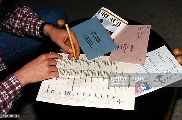 ein Wähler füllt einen Stimmzettel aus daneben eine Urlaubsbroschüre und ein amtlicher Wegweiser zur Briefwahl 1995