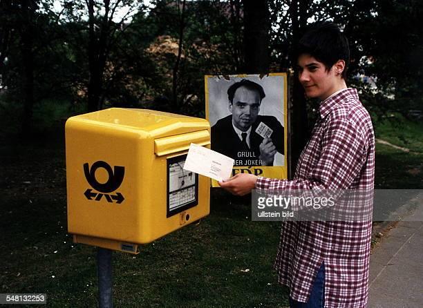 eine Wählerin steckt einen Briefwahlumschlag in einen Breifkasten dahinter ein Wahlplakat der FDP 1995