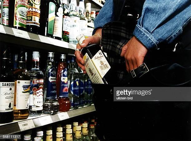 Symbolfoto Ladendiebstahl Kundin steckt eine Flasche Whisky in ihre Tasche 1996