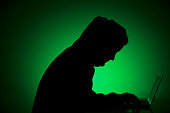 Symbolic feature with topic online crime data theft and piracy and hacker here the silhouette of a person with a laptop in his hands on Augut 20 2015...