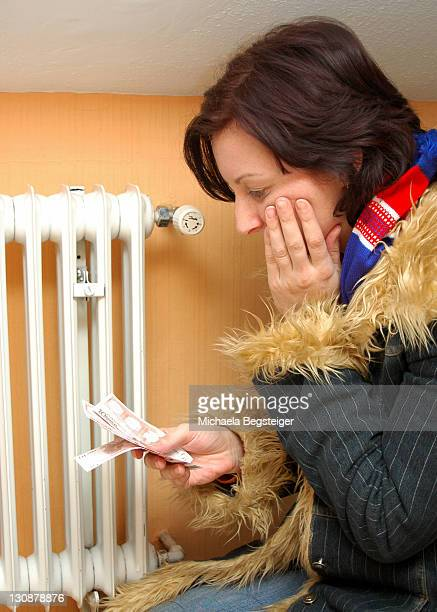 Symbolic for heating costs, woman with money freezing next to ratiator
