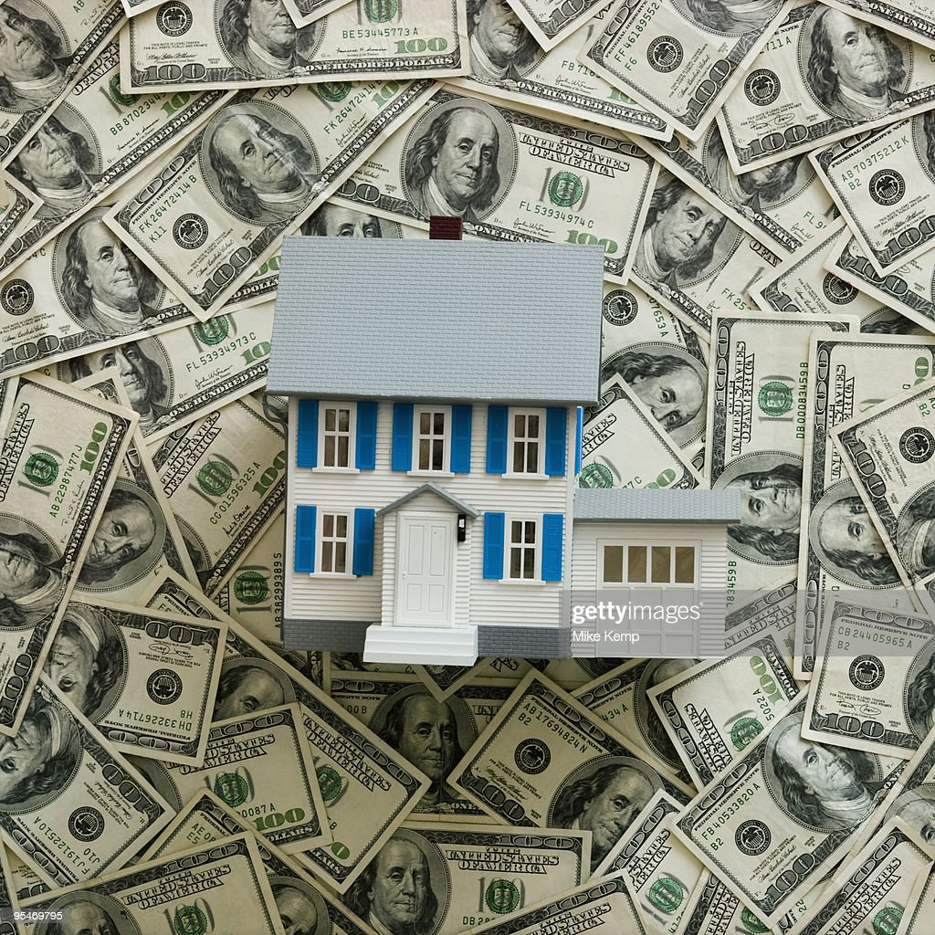 Symbolic house wtih US dollars as background