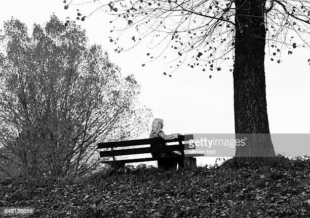 symbolic loneliness young woman sitting on a bench under a tree autumnal backlight silhouette aged 25 to 35 years Elisabeth