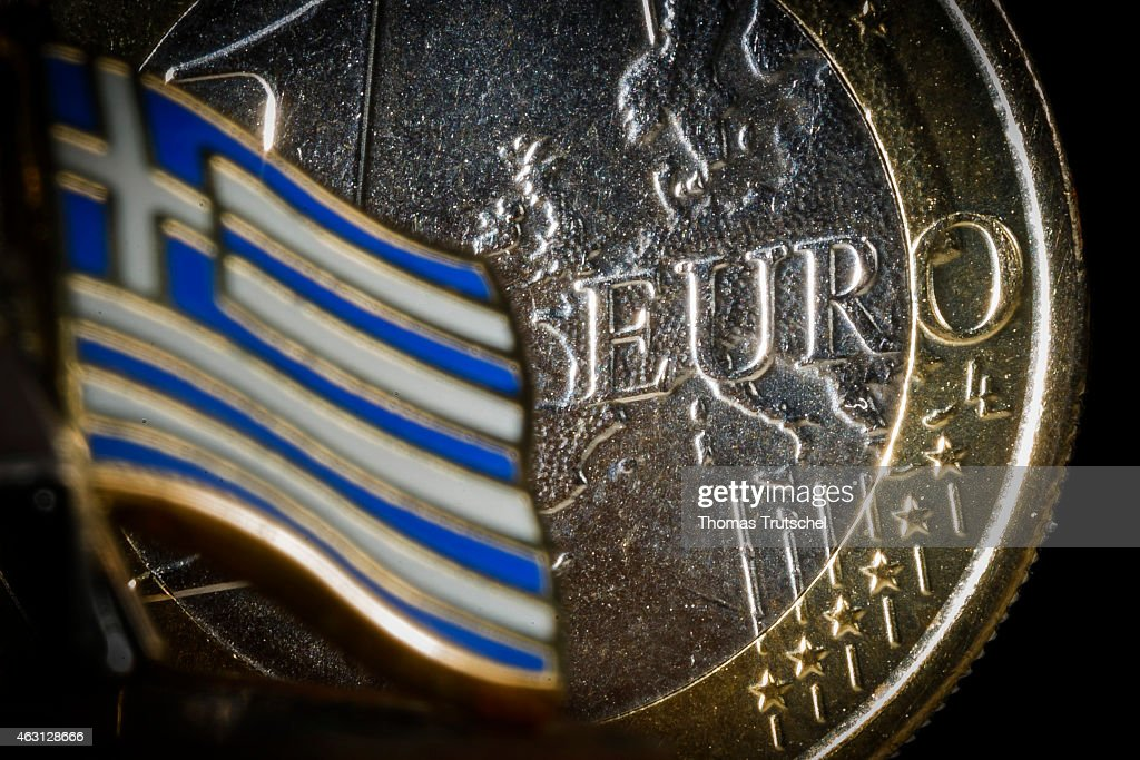 Symbolic photo of Greece and the Euro, one euro coin behind the national flag of Greece on February 10, 2015 in Berlin, Germany. Greek withdrawal from the eurozone is the potential discontinuation of the euro as the national currency of Greece and the resulting Greek exit from the eurozone monetary union.