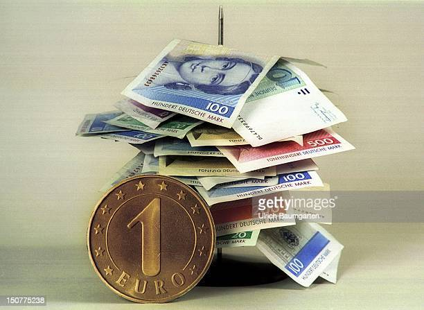 Symbolic photo to the topic 'EURO' a 1 EURO coin and speared DM notes