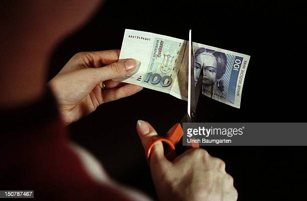A symbolic photo to the topic of the drop in of the interesttax A 100 DM note has been cut into onethird with a pair of scissors