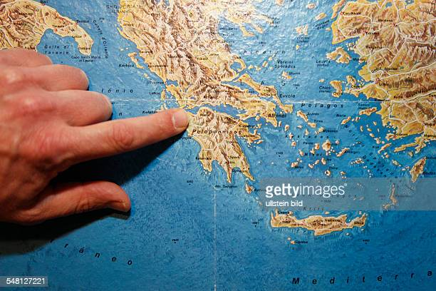 symbolic photo travel geography finger on a map Greece