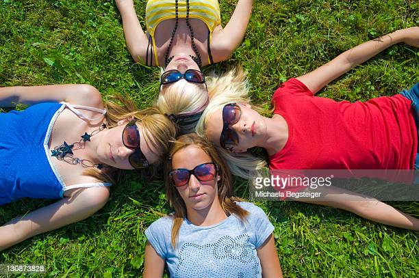 Symbolic picture for circle of friends, teenage girls lying head to head on a meadow