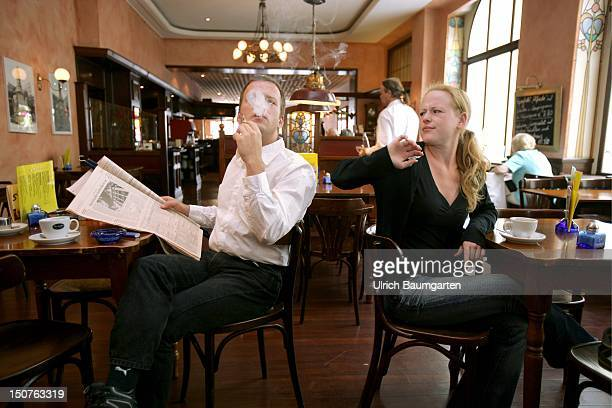 Symbolic picture to the topics passive smoking smoking addiction Our picture shows a smoker smoked a cigarette at a cafe shirty guests