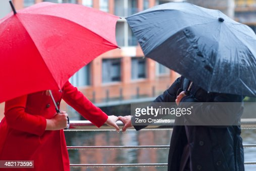 Symmetrical couple holding handrail and carrying umbrella's