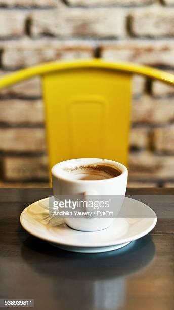 Symmetrical Image Of Cup Of Coffee On Table And Yellow Chair Behind