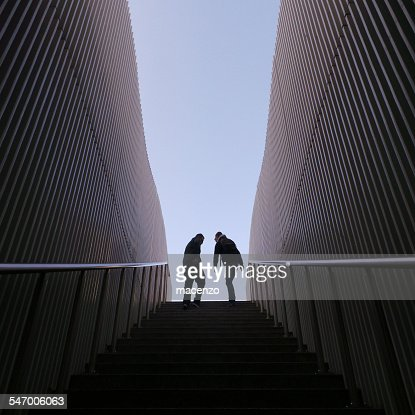 Symmetrical image of two silhouette people on top of stairs, walls on sides