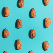 Symmetrical pattern of almonds on blue. Flat lay.