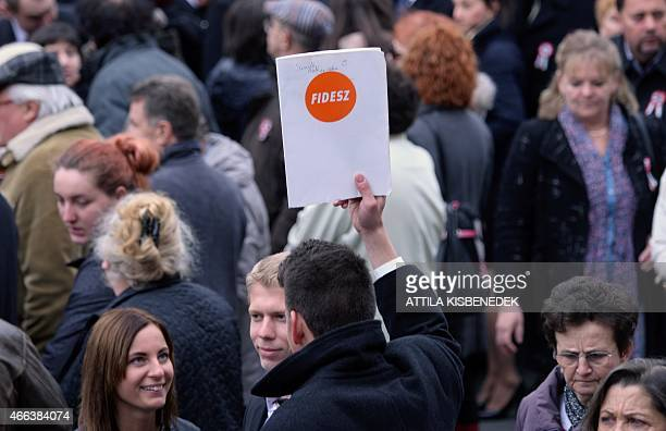 A sympathizer of Hungarian Prime minister's Victor Orban's FIDESZ party lifts a paper in the crowd in front of the National Museum of Budapest on...