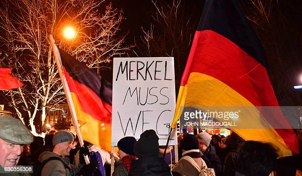 Sympathizers of German populist party AfD hold a placard reading 'Merkel has to leave' during a prostest rally in front of the chancellory in Berlin...
