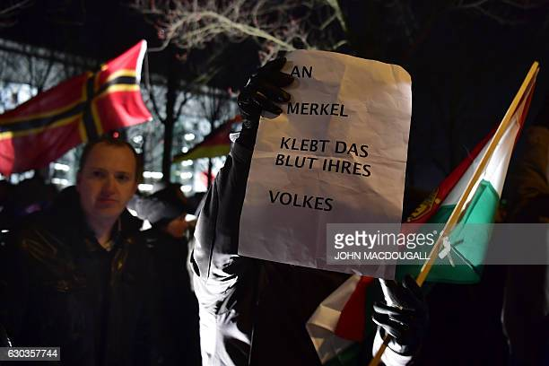 Sympathizers of German populist party AfD hold a placard reading 'Merkel has blood of her nation on her hands' during a prostest rally in front of...