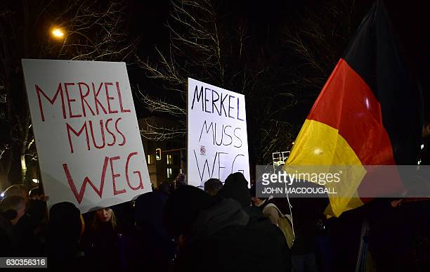 Sympathizers of German populist party AfD hold placards reading 'Merkel has to leave' during a prostest rally in front of the chancellory in Berlin...