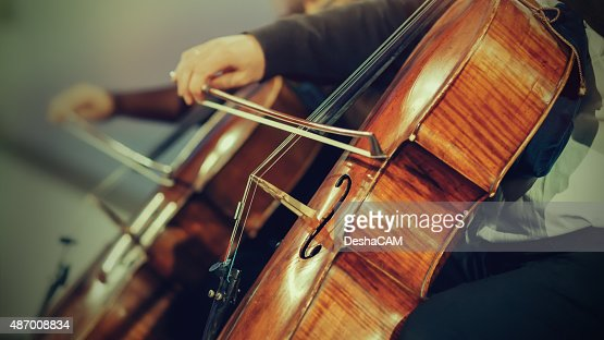 Symphony orchestra on stage, hands playing cello : Stock Photo