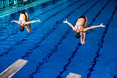 Synchronized diving. Two female springboard divers in the air