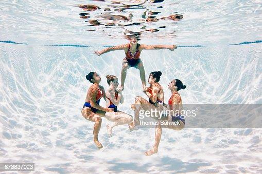 Synchronized swim team preparing to perform lift