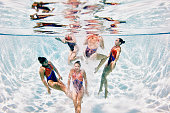 Synchronized swimmers swimming to surface