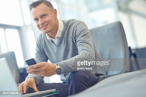 Syncing his smartphone and laptop : Stock Photo