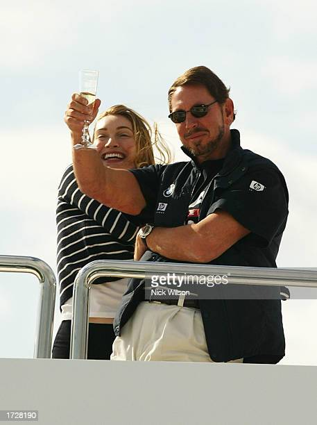 Syndicate head of Oracle Larry Ellison with his fiancee Melanie Croft celebrate his team's win after race four of the Louis Vuitton Cup Final between...