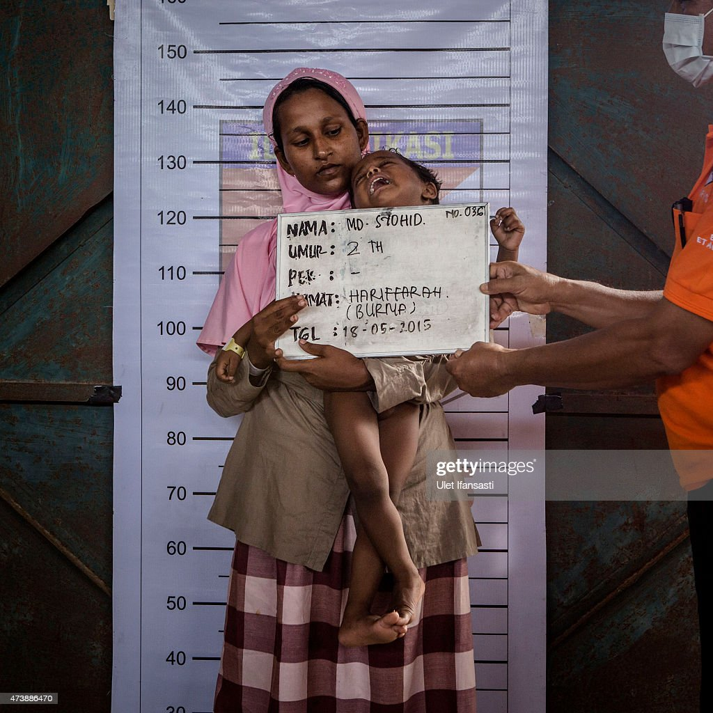 Syohid 2, a Rohingya migrant child is held by his mother as his picture is taken during identification purposes at a temporary shelter on May 18, 2015 in Kuala Langsa, Aceh province, Indonesia. Hundreds of Myanmar's Rohingya refugees arrived in Indonesia on May 15, many requiring medical attention. Thousands more are believed to still be stranded at sea reportedly with no country in the region willing to take them in. Myanmar's Rohingya Muslim community have long been persecuted and marginalized by Myanmar's mostly Buddhist population.