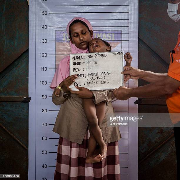 Syohid 2 a Rohingya migrant child is held by his mother as his picture is taken during identification purposes at a temporary shelter on May 18 2015...