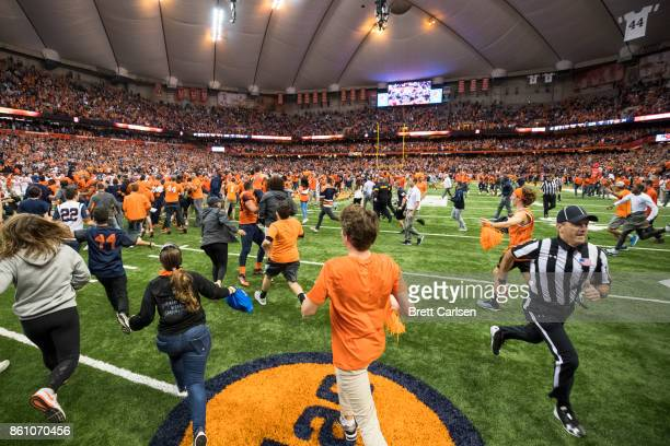 Syracuse Orange fans storm the field after the team upset Clemson Tigers at the Carrier Dome on October 13 2017 in Syracuse New York Syracuse defeats...