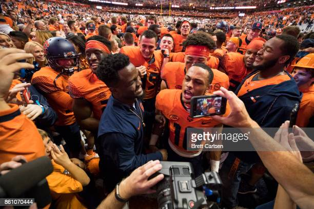 Syracuse Orange players celebrate an upset over Clemson Tigers after fans stormed the field at the Carrier Dome on October 13 2017 in Syracuse New...