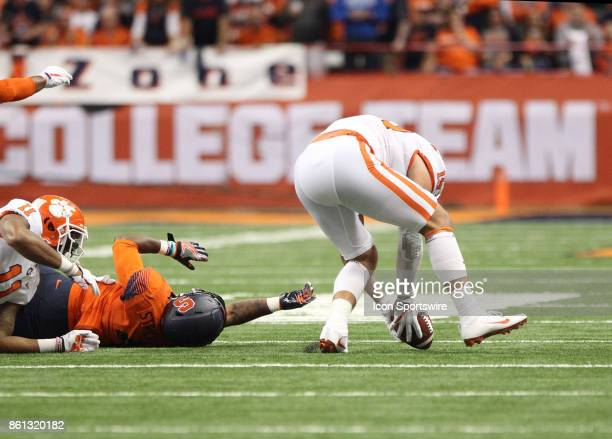 Syracuse Orange running back Dontae Strickland lays on the field after fumbling the football Clemson Tigers safety Tanner Muse picks up the ball and...