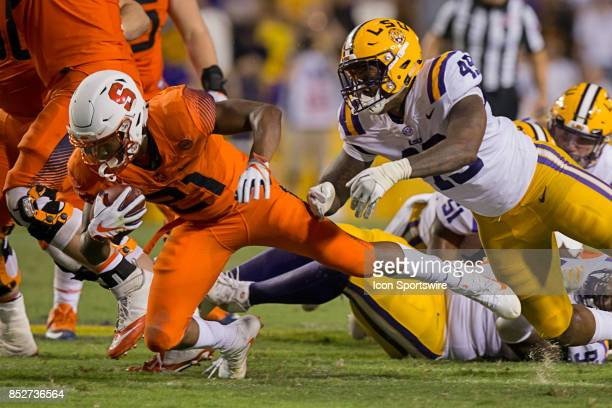 Syracuse Orange running back Moe Neal is tackled boy LSU Tigers linebacker Arden Key during a college football game between the LSU Tigers and the...
