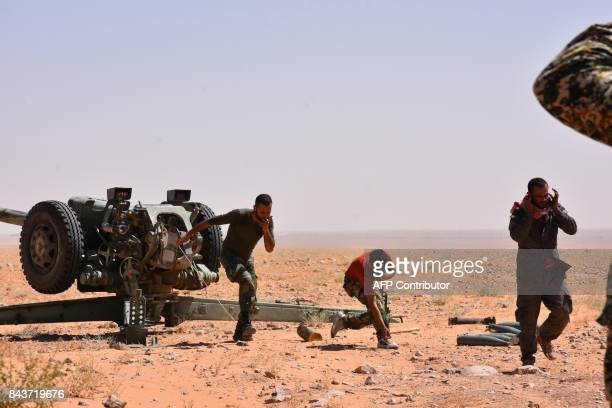 TOPSHOT Syria government forces fire artillery shells as they advance in AlShula on the southwestern outskirts of Deir Ezzor on September 7 during...